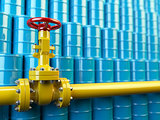 Yellow gas pipe line valves and blue oil barrels. Fuel and energ