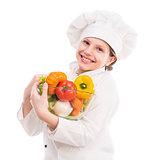 little girl-cook with bowl of vegetables on shoulder
