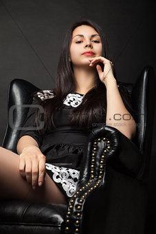beautiful woman in big black leather armchair