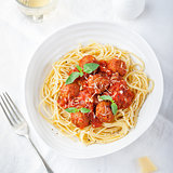 Meatballs in tomato sauce and fresh basil with spaghetti on a white plate Top view