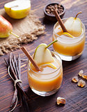 Pear mulled cider with vanilla and cinnamon sticks on a wooden background