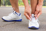 Men is tying shoes laces for jogging at park.