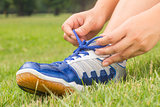 Girl is tying shoes laces for jogging at park.