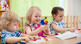 Kids making arts and crafts. Children in kindergarten.