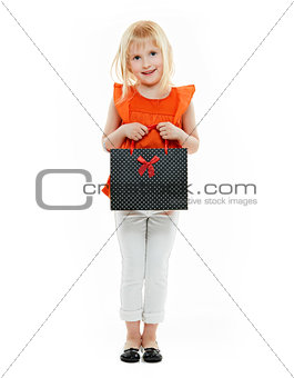 Blond girl in orange shirt with shopping bag on white background