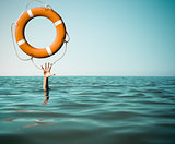 Drown man with rised hand getting lifebuoy help in sea