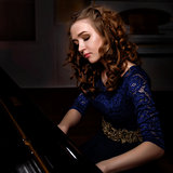 Young woman playing the grand piano