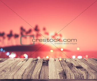 3D wooden deck looking out to a palm tree island at sunset