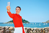 Happy woman taking selfie in front of lagoon with yachts