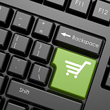Green enter button with shopping cart on black keyboard, isolate