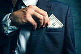 Businessman putting dollar banknotes money in his suit pocket
