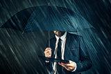 Businessman reading business news on digital tablet in rain