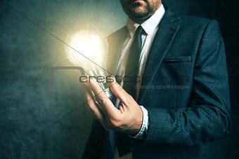 Business creativity concept with businessman holding light in ha