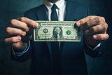 Businessman holding one USA dollar bill