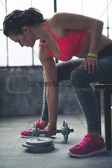 Fitness woman taking dumbbell from the floor in urban loft gym