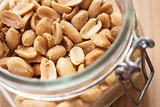 Open canning jar with fried salty peanuts. Overhead view