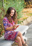 Happy woman in a dress sitting on a bench and writing sms