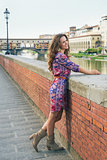 Happy young woman in a dress on embankment near Ponte Vecchio