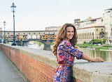 Smiling young woman in a dress on embankment near Ponte Vecchio