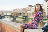 Smiling woman sitting on the embankment near Ponte Vecchio