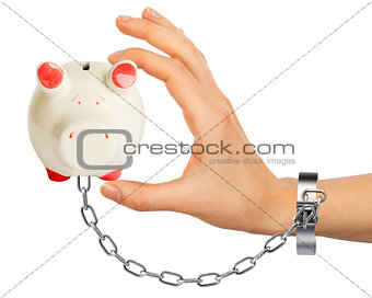 Chained hand holding piggy bank