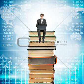 Businessman with laptop sitting on stack of books