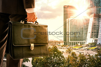 Businessman with suitcase against modern city