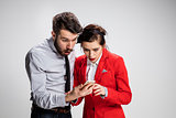 Business concept. The two young colleagues holding mobile phone on gray background