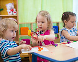 Kids or children creating arts and crafts in kindergarten. Girl is communicating with boy.