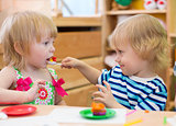 Two kids playing in kindergarten together. Boy feeding girl.