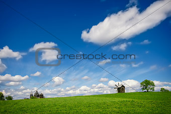 Green lanscape with one old windmill