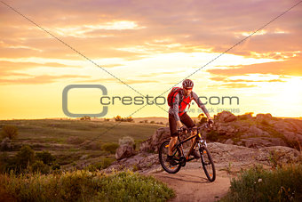 Cyclist Riding the Bike on Mountain Rocky Trail at Sunset