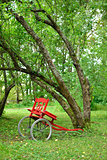 Red cart next to leaning trees