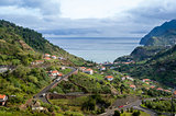 Typical landscape of Madeira island, serpentine mountain road, houses on the hills and ocean view
