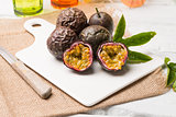 Passion fruits on white ceramic tray on wooden table background.