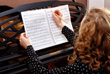 Young woman musician writes in music book pencil.