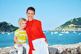Happy mother and child in front of lagoon with yachts