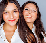cute pretty teen daughter with mature mother hugging, fashion style brunette makeup