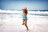 Baby girl running on a beach