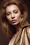 Beautiful girl in a gold dress with creative makeup and hair. The beauty of the face.