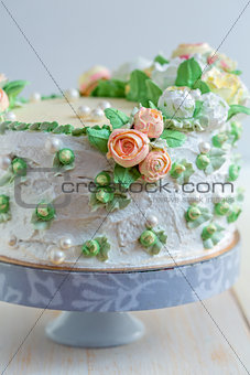 Cake with cream roses and sugar pearls.