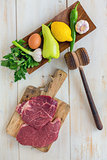 Raw beef for schnitzel and vegetables on wooden plate. View from