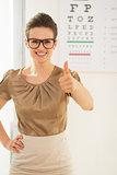 Woman wearing eyeglasses showing thumbs up near Snellen chart