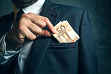 Businessman putting euro banknotes money in his suit pocket