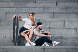 Young stylish couple on concrete stairs with a longboard