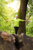 Woman holding balance on tree trunk in nature.