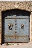 Old iron door with lion handles on a stone wall