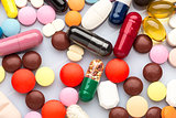 Scattered colorful medical pills and capsules