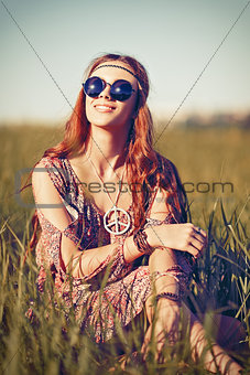 Portrait of beautiful young hippie girl in the field