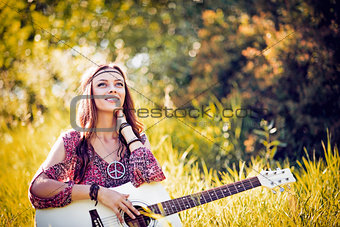 Portrait of beautiful smiling hippie girl with guitar. Outdoor shot
